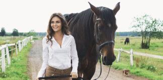 Junge Reiterin beim Spaziergang mit ihrem Pferd