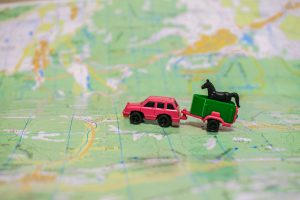 Ein Spielzeugauto mit Anhänger zum Transport eines Pferdes.
